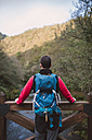 Hiker standing on bridge above a river looking at view - RAEF01563