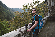 Hiker standing at stone wall looking around - RAEF01572