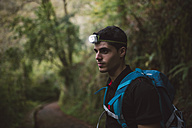 Hiker with a headlamp in the forest - RAEF01578