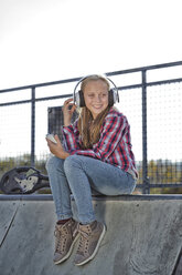 Portrait of smiling skateboarder listening music with headphones in a skatepark - MAEF12052