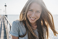 Portrait of happy young woman on jetty at backlight - KNSF00666