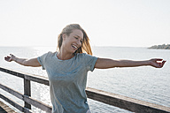 Happy young woman on jetty at backlight - KNSF00669