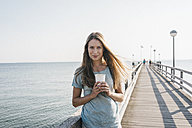 Portrait of happy young woman with coffee to go on jetty - KNSF00672