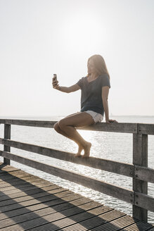 Young woman sitting on jetty at backlight taking selfie with cell phone - KNSF00678