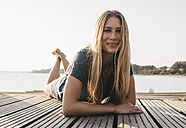Portrait of happy young woman laying on jetty - KNSF00681