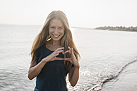 Portrait of happy young woman at seafront - KNSF00684