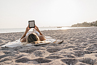Young woman lying on blanket on the beach using tablet - KNSF00687