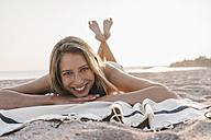 Happy young woman lying on blanket on the beach - KNSF00690