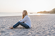 Young woman sitting on the beach in the evening - KNSF00696