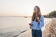 Smiling young woman lwith smartphone standing on the beach - KNSF00699