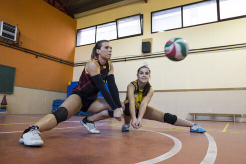Two volleyball players digging the ball during a volleyball match - ABZF01561