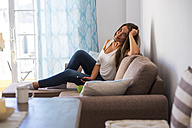Young woman sitting on the couch with remote control - SIPF01123