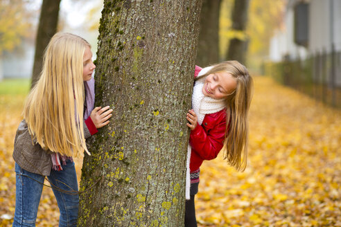 Two girls playing hide and seek in autumn - MAEF12063