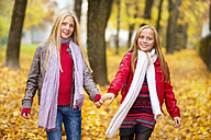 Two happy girls hand in hand in autumn - MAEF12066