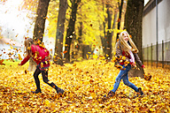 Two girls playing with autumn leaves - MAEF12069