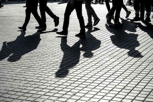 Shadows of people walking on pavement - EJW00809
