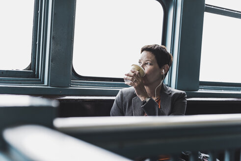 Businesswoman on a ferry drinking coffee - UU09329