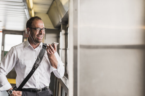 Laughing businessman on a ferry with cell phone and earphones - UU09341