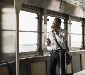 Businessman on a ferry looking out of window - UU09344