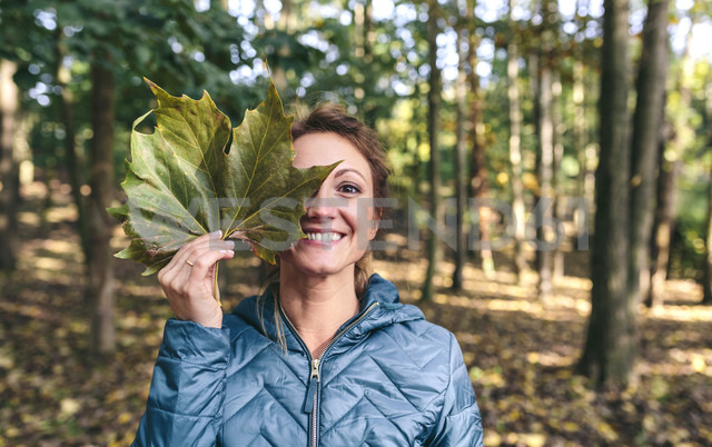 Grinning woman covering eye with  autumn leaf in the forest - DAPF00472 - David Pereiras/Westend61