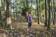 Happy little girl jumping in the air in the woods - DAPF00478