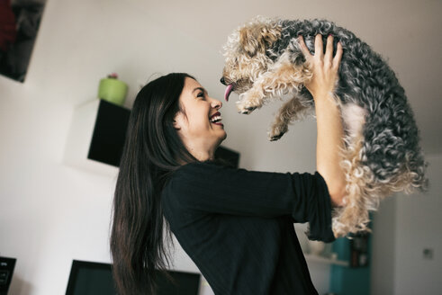 Happy young woman with her dog at home - JASF01301