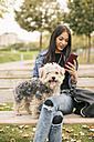 Young woman sitting on bench in a park with her dog looking at cell phone - JASF01313