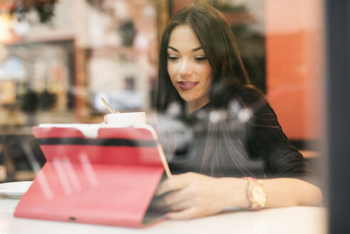 Young woman sitting behind windowpane of a coffee shop looking at tablet - JASF01316