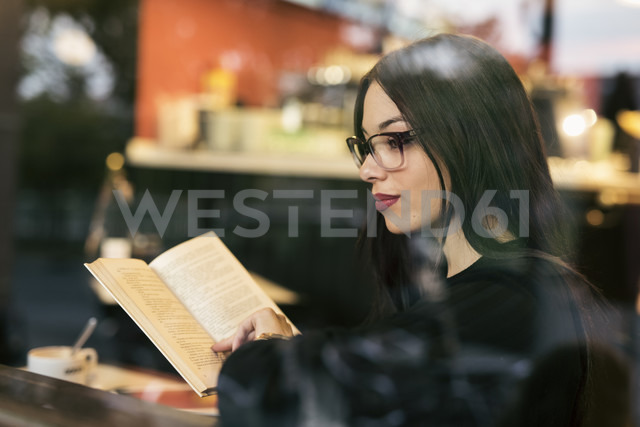 Pensive young woman sitting behind windowpane of a coffee shop with a book - JASF01319
