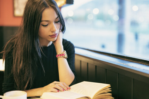 Young woman sitting in a coffee shop reading a book - JASF01322
