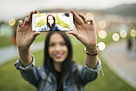 Young woman taking selfie with cell phone at twilight - JASF01325