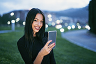 Portrait of smiling young woman with smartphone at twilight - JASF01328