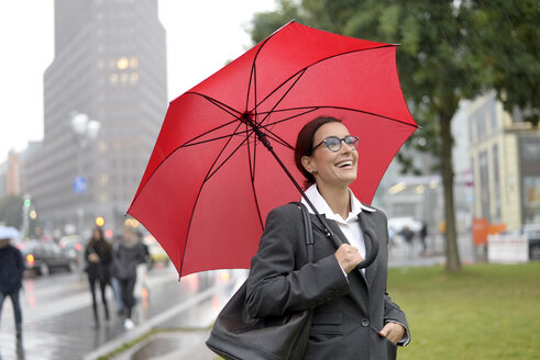 Germany, Berlin, happy businesswoman with red umbrella at Potsdamer Platz - BFRF01790