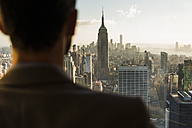 USA, New York City, man looking on cityscape on Rockefeller Center observation deck - UU09352