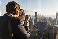 USA, New York City, man looking through coin-operated binoculars on Rockefeller Center observation deck - UU09358