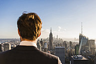 USA, New York City, man looking on cityscape on Rockefeller Center observation deck - UU09361
