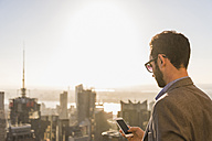 USA, New York City, businessman with cell phone on Rockefeller Center observation deck - UU09364