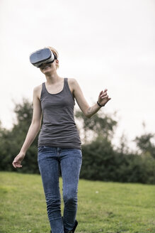 Smiling young woman using Virtual Reality Glasses outdoors - TAMF00835