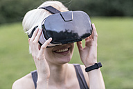 Smiling young woman using Virtual Reality Glasses outdoors - TAMF00838