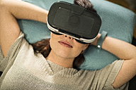 Young woman using Virtual Reality Glasses at home - TAMF00847