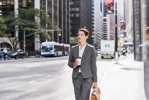 USA, New York City, businesswoman in Manhattan with takeaway coffee - UUF09384