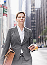 USA, New York City, businesswoman in Manhattan with cell phone - UUF09390