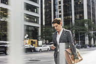 USA, New York City, businesswoman in Manhattan looking on cell phone - UUF09393
