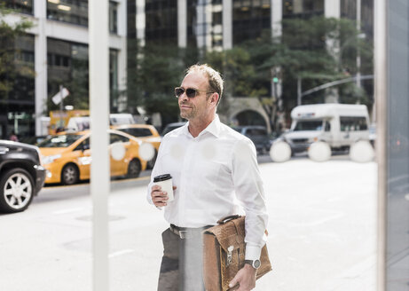 USA, New York City, confident businessman in Manhattan with takeaway coffee - UUF09396
