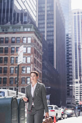 USA, New York City, businesswoman in Manhattan with with cell phone and earphones - UUF09402