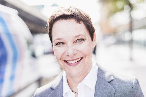 Portrait of smiling businesswoman outdoors - UUF09405