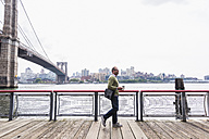 USA, New York City, man walking at East River - UUF09417