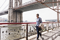 USA, New York City, woman walking at East River - UUF09420
