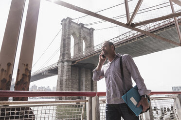 USA, New York City, man at East River talking on cell phone - UUF09423
