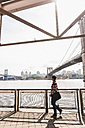 USA, New York City, woman walking at East River - UUF09426